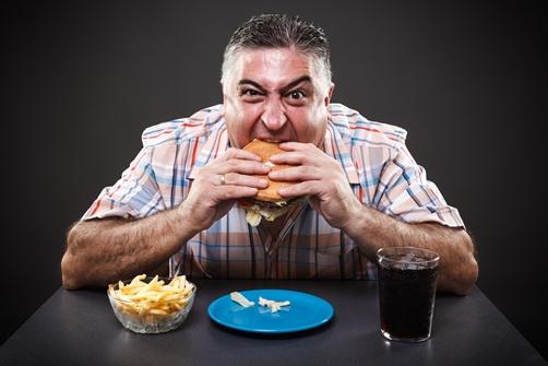 גבר עצבני אוכל המבורגר